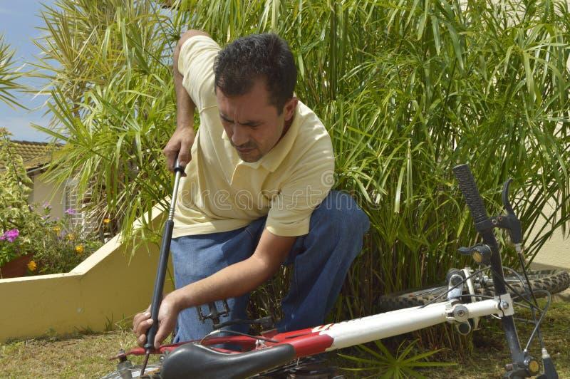 Homme d'une cinquantaine d'années gonflant la bicyclette photographie stock