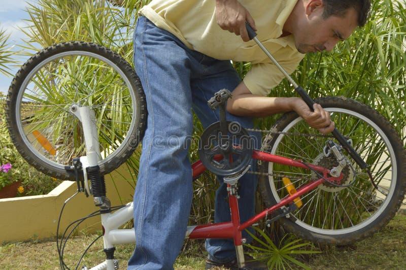 Homme d'une cinquantaine d'années gonflant la bicyclette photos stock