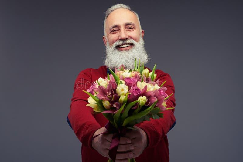 Homme d'une cinquantaine d'années positif avec une barbe dans les WI rouges de chandail images libres de droits