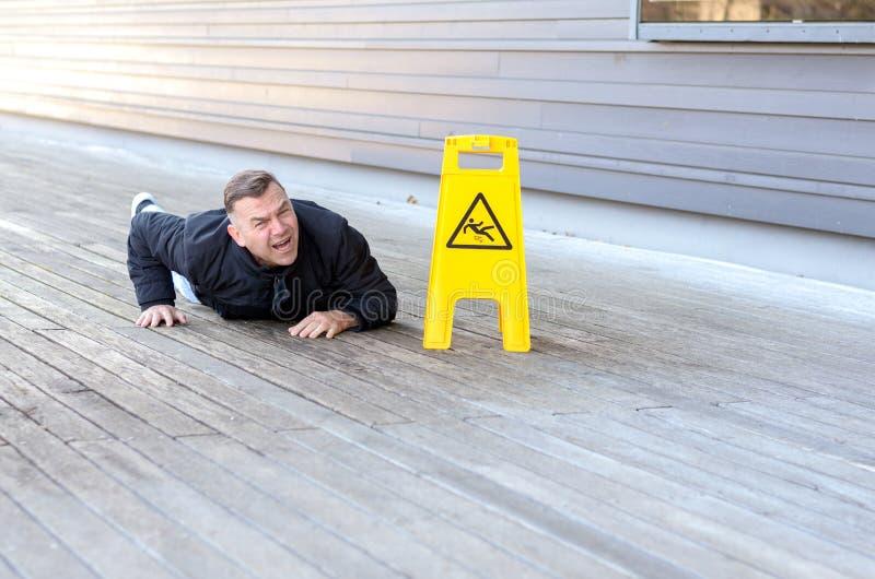 Homme d'une cinquantaine d'années pris une chute sur un plancher glissant photos stock