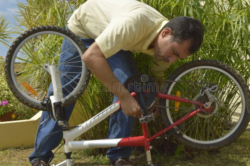 Homme d'une cinquantaine d'années réparant une bicyclette photo libre de droits