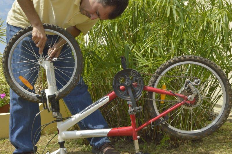 Homme d'une cinquantaine d'années réparant une bicyclette image libre de droits