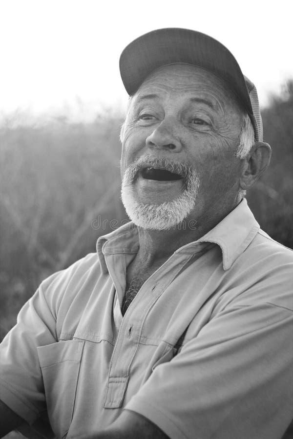 Homme d'une cinquantaine d'années riant dans une casquette de baseball photographie stock