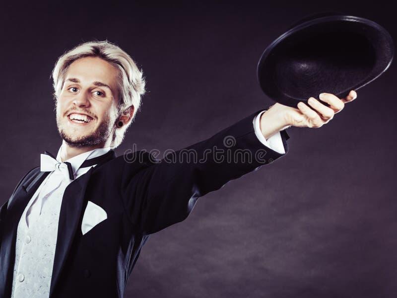 Homme d'une manière élégante habillé jetant le chapeau noir de chapeau feutré photographie stock libre de droits