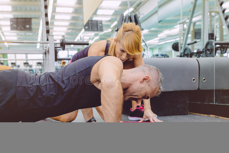 Homme d'une manière encourageante de muscle d'entraîneur personnel dans la poussée photos libres de droits