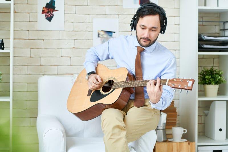 Homme dans des écouteurs jouant la guitare image stock