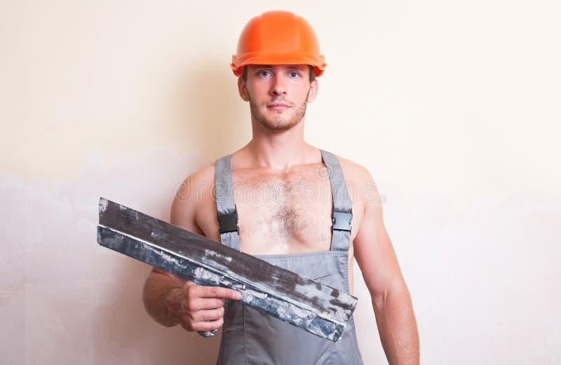 Homme dans des combinaisons avec une grande spatule images stock