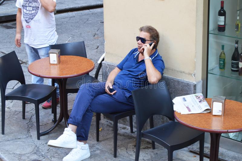 Homme dans des lunettes de soleil se reposant en café extérieur appréciant le temps libre parlant au téléphone portable, Italie,  image libre de droits
