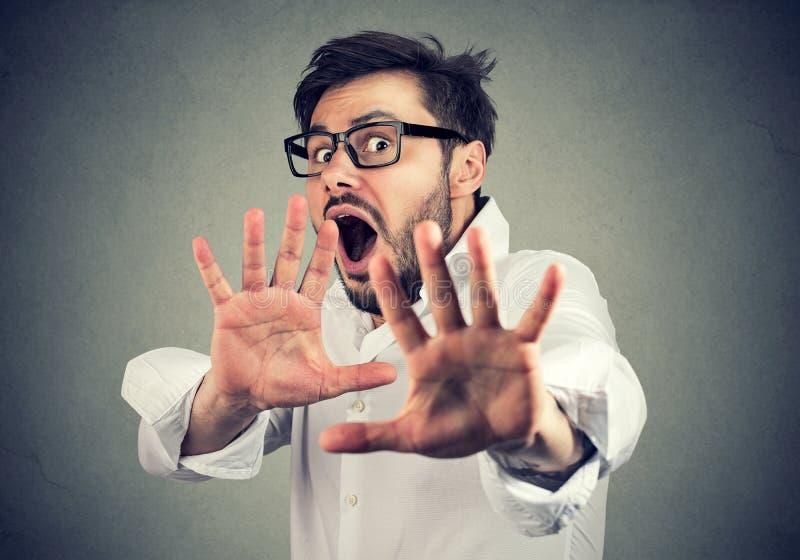 Homme dans des mains tendantes de panique à l'appareil-photo photo libre de droits