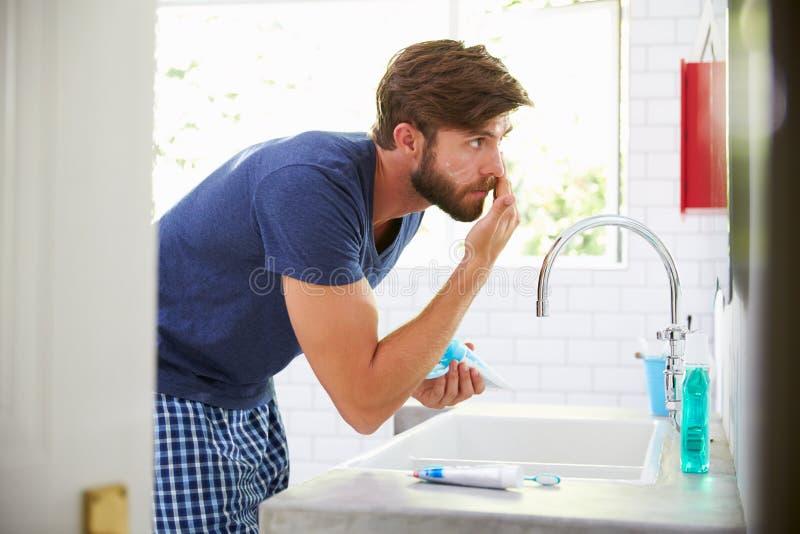 Homme dans des pyjamas mettant sur la crème hydratante dans la salle de bains images libres de droits