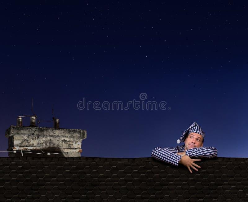 Homme dans des pyjamas s'élevant sur le toit images libres de droits