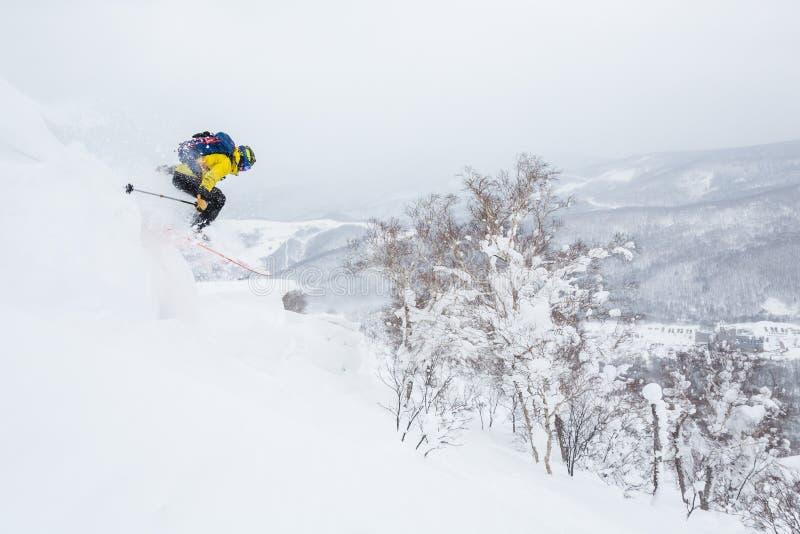 Homme dans des sauts jaunes outre d'une corniche près du sommet d'une petite crête dans le backcountry du Hokkaido, Japon photos stock