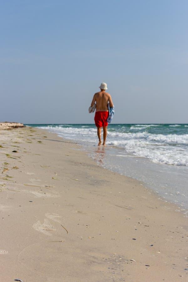 Homme dans des shorts rouges avec le chapeau et la serviette de Panama blancs au bord de la mer le jour ensoleillé d'été photographie stock