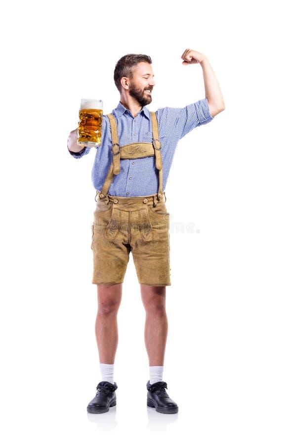 Homme dans des vêtements bavarois, tenant la bière, montrant le biceps image libre de droits