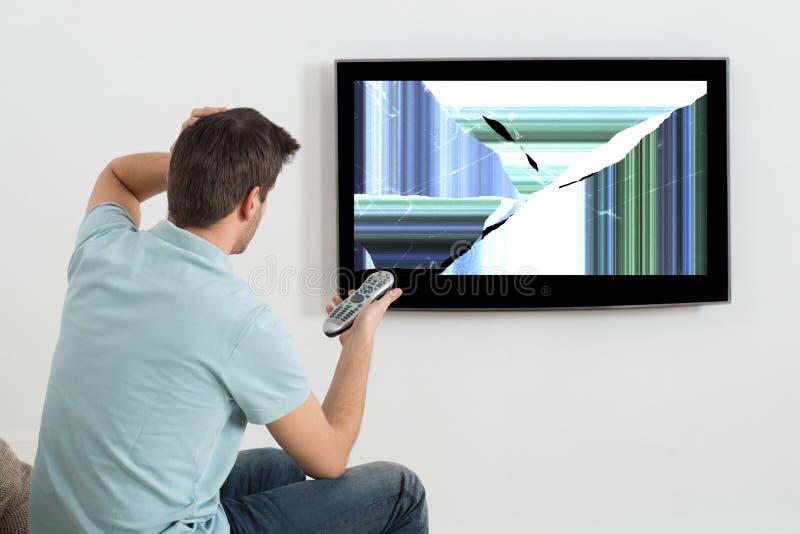Homme dans l'écran de Front Of Television Showing Distorted images stock