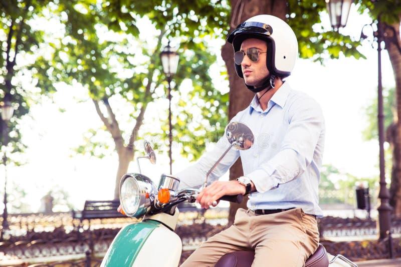 Homme dans l'équitation de casque sur le scooter image libre de droits