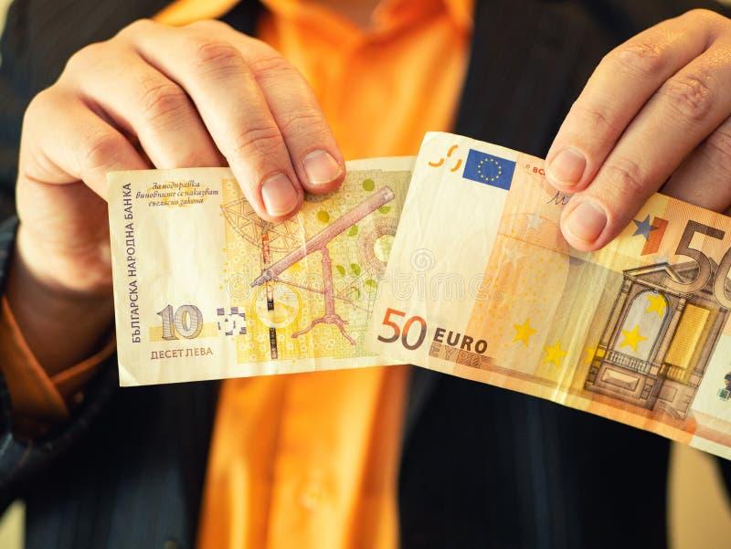 Homme dans l'argent et les euros bulgares de lev d'exposition de costume photo stock