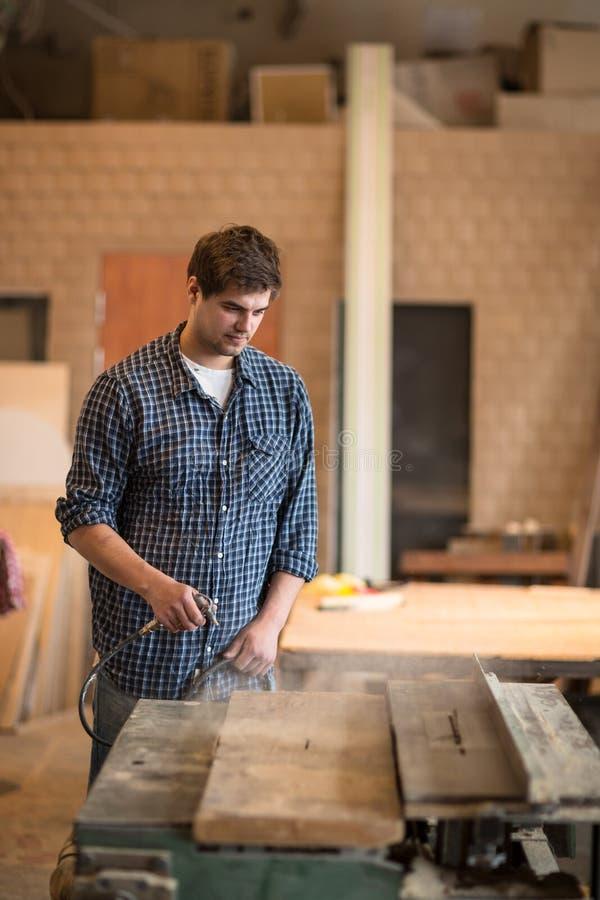 Homme dans l'atelier, atelier de menuiserie rangeant, saupoudrage pneumatique image stock