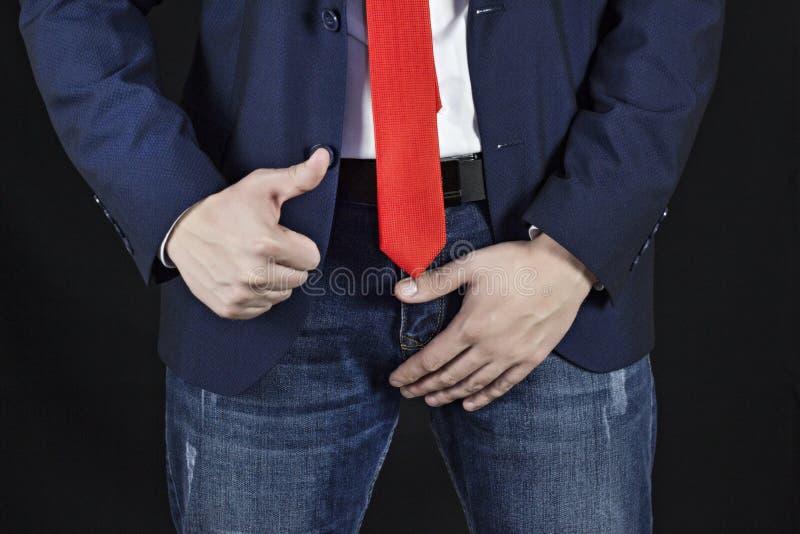 Homme dans l'homme d'affaires de costume tenant dessus le secteur inguinal et montrant la classe de geste, problèmes noirs de mâl image stock