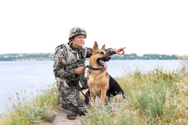 Homme dans l'uniforme militaire avec le chien de berger allemand photo libre de droits