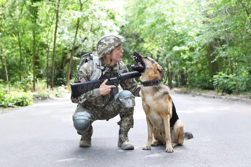 Homme dans l'uniforme militaire avec le chien de berger allemand photo stock