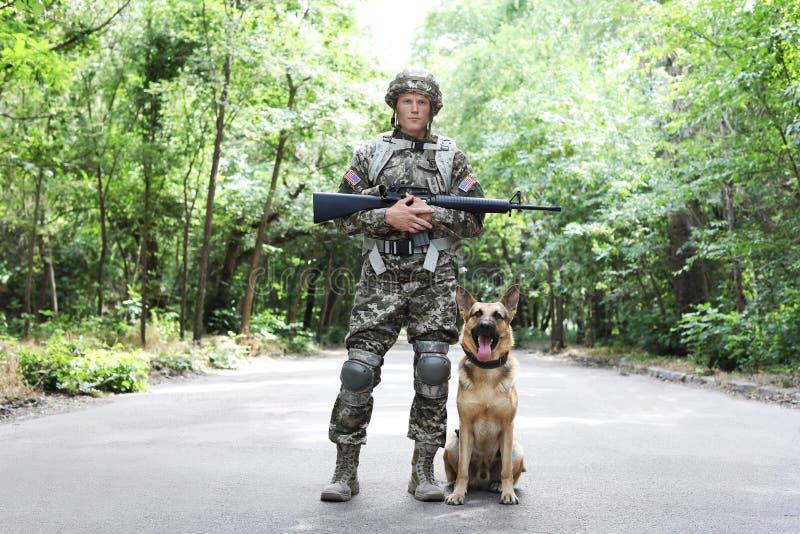 Homme dans l'uniforme militaire avec le chien de berger allemand images libres de droits