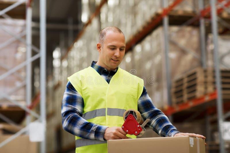 Homme dans la caisse d'emballage de gilet de sécurité à l'entrepôt photo libre de droits