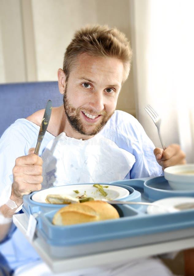 Homme dans la chambre d'hôpital mangeant de la nourriture de clinique d'alimentation saine dans l'expression satisfaisante heureu photographie stock