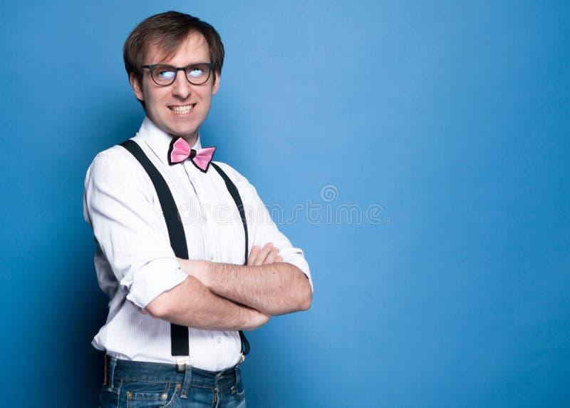 Homme dans la chemise, la bretelle, le noeud papillon rose et la position en verre, souriant avec les bras croisés photographie stock