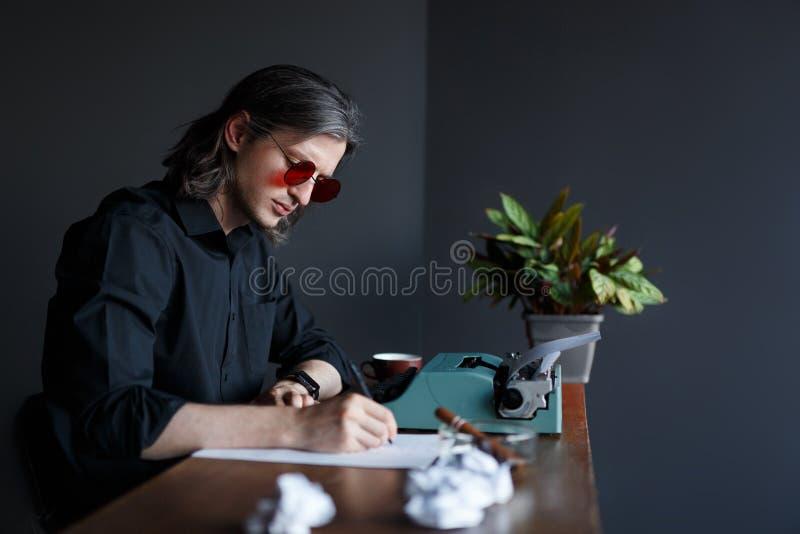 Homme dans la chemise noire et des lunettes de soleil rouges, écrivant une lettre sur le papier, posé à la table avec la machine  photo libre de droits