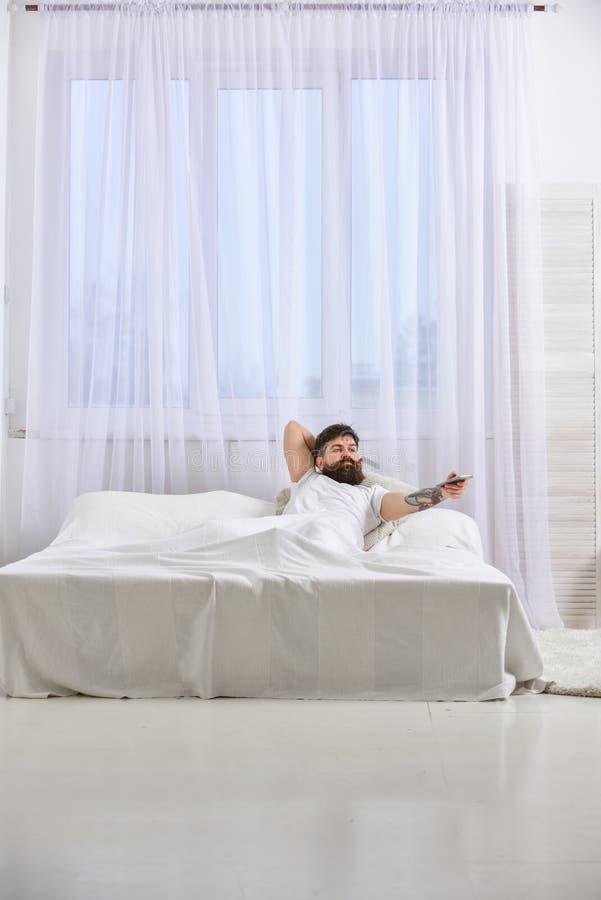 Homme dans la chemise s'étendant sur le lit, TV de observation, rideaux blancs sur le fond Type sur le visage sérieux utilisant à photographie stock libre de droits