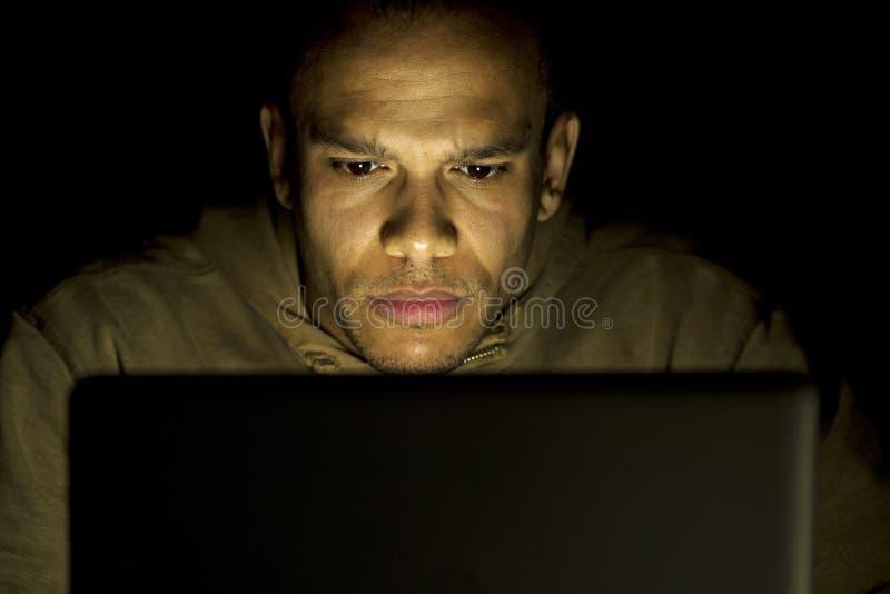 Homme dans la concentration sérieuse tandis que sur son ordinateur portable tard la nuit image libre de droits