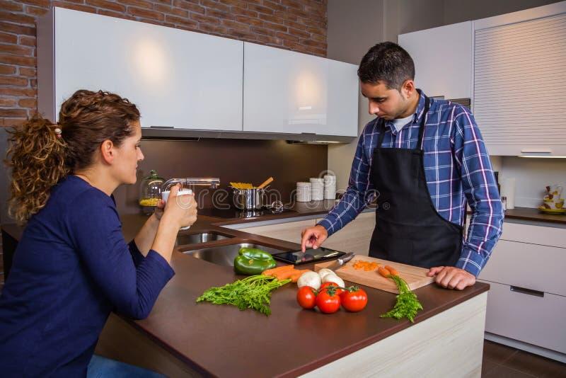 Homme dans la cuisine à la maison regardant la recette avec le comprimé électronique images stock