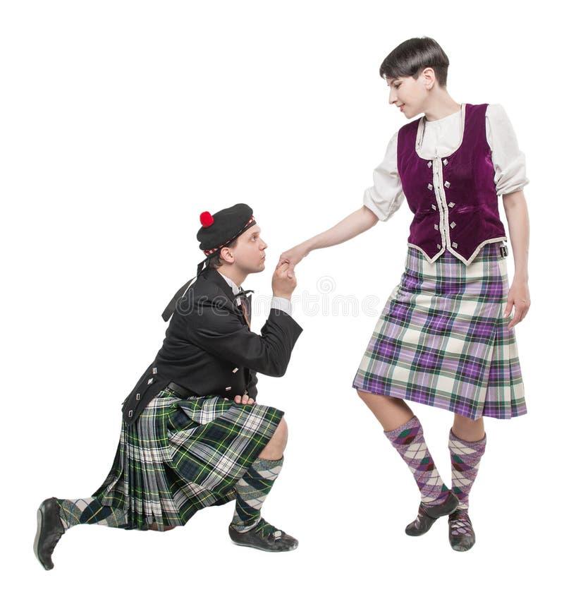 Homme dans la main de baiser de femme de costume écossais de traditioanl image stock