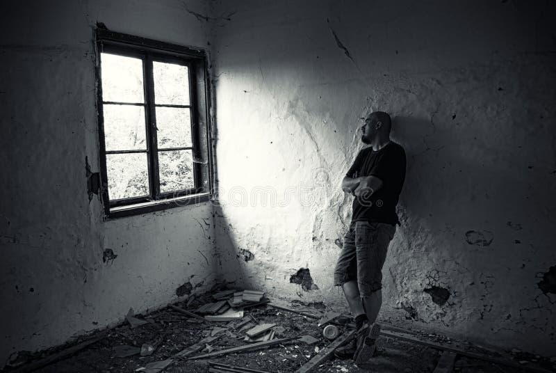 Homme dans la maison ruinée image stock