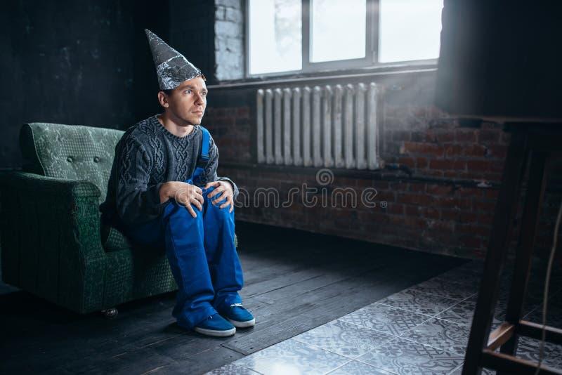 Homme dans la montre TV, phobie de chapeau de feuille d'étain de télépathie photos libres de droits