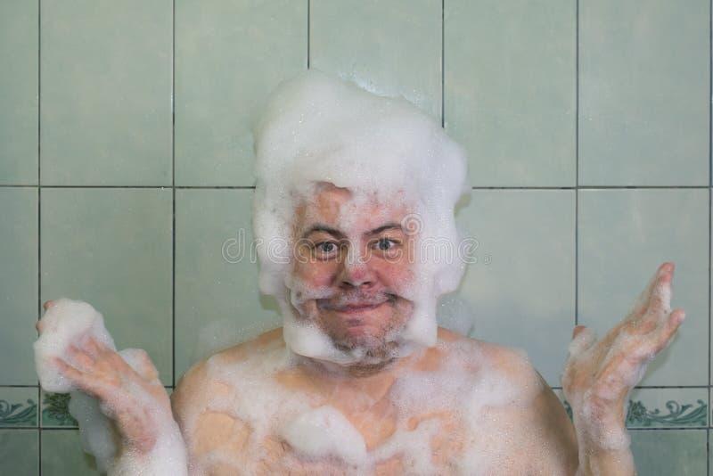 Homme dans la mousse dans la salle de bains image stock