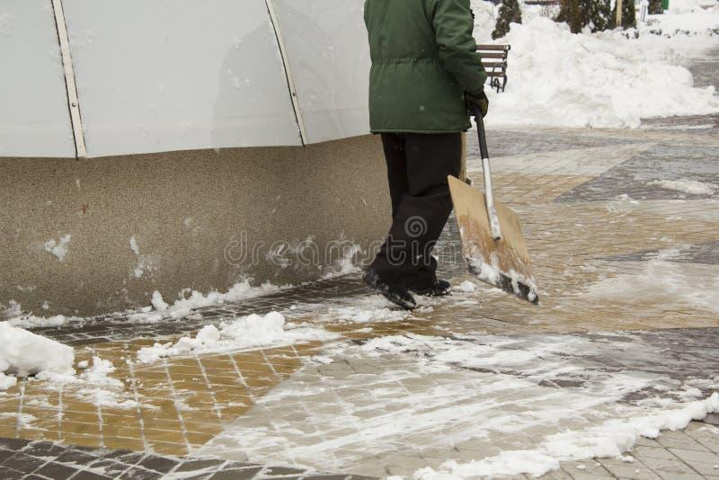 Homme dans la neige de nettoyage uniforme avec une pelle images libres de droits