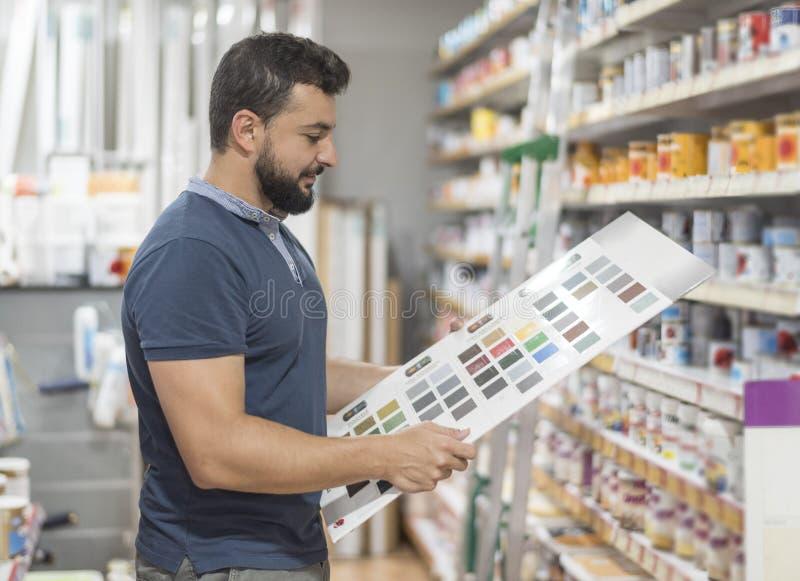 Homme dans la pharmacie choisissant la couleur de peinture pour son travail photos libres de droits