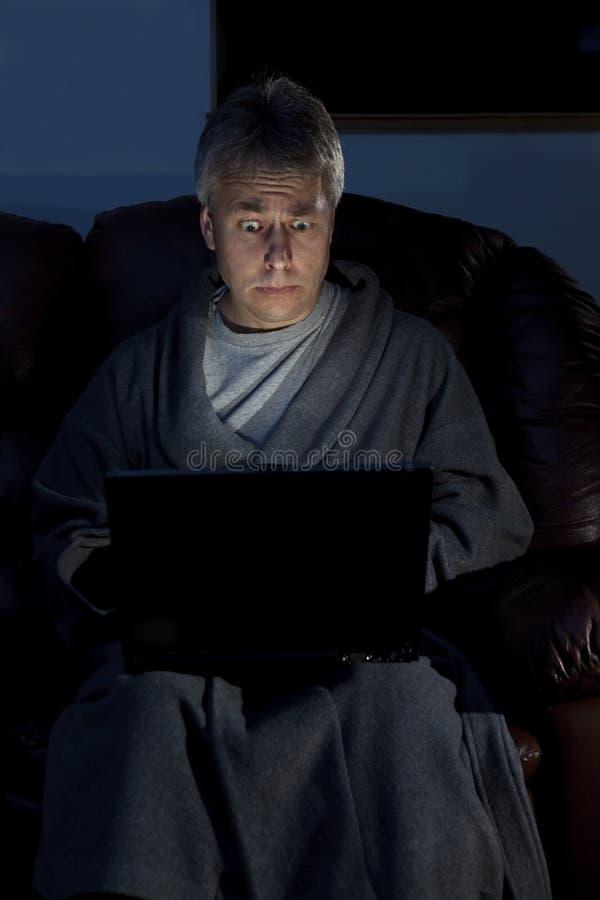 Homme dans la robe d'intérieur fonctionnant la série tardive photos libres de droits