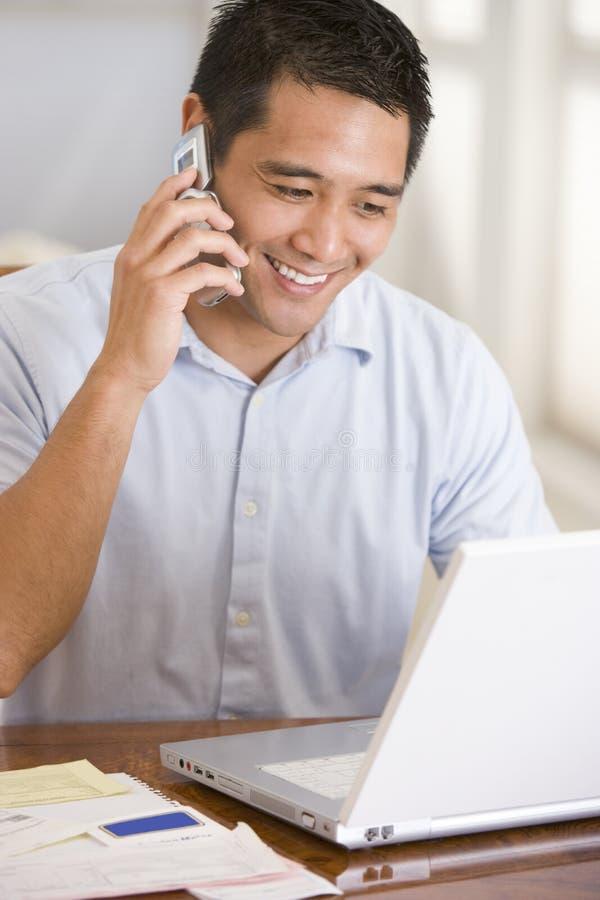 Homme dans la salle à manger sur le téléphone mobile utilisant l'ordinateur portatif photographie stock libre de droits