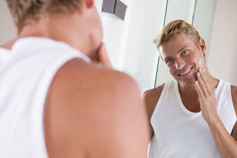 Homme dans la salle de bains appliquant la crème de visage photos stock