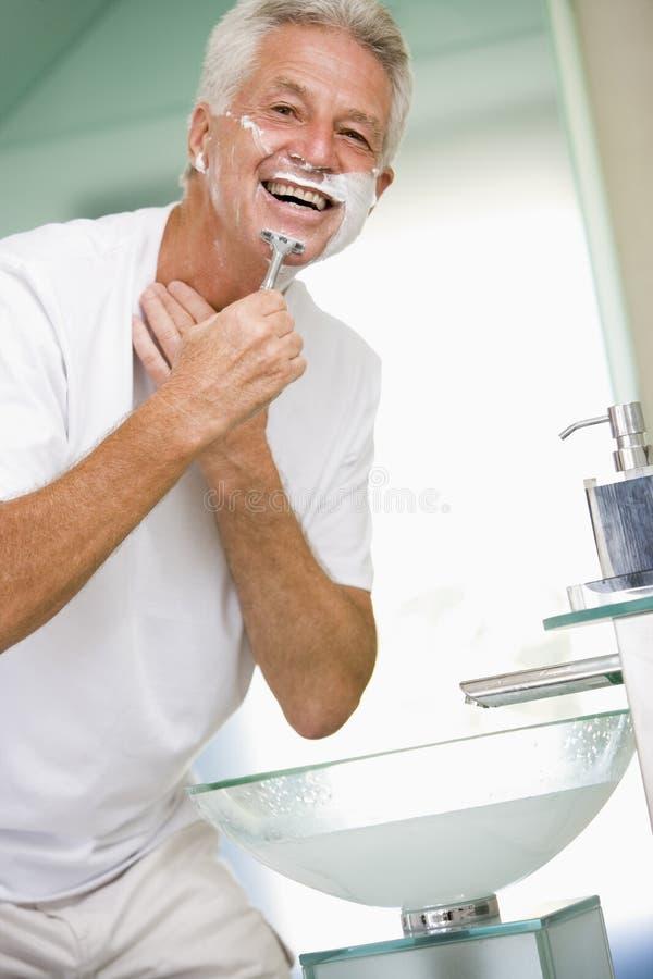 Homme dans la salle de bains rasant et souriant photo for Salle de bain homme