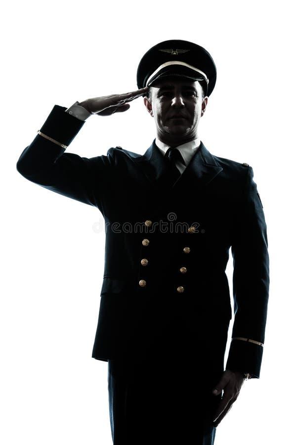 Homme dans la salutation uniforme de silhouette de pilote de compagnie aérienne photographie stock libre de droits