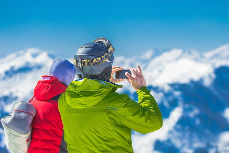 Homme dans la veste verte et le Gray Helmet Holding Phone Standing à côté de la personne dans la veste rouge et noire image stock