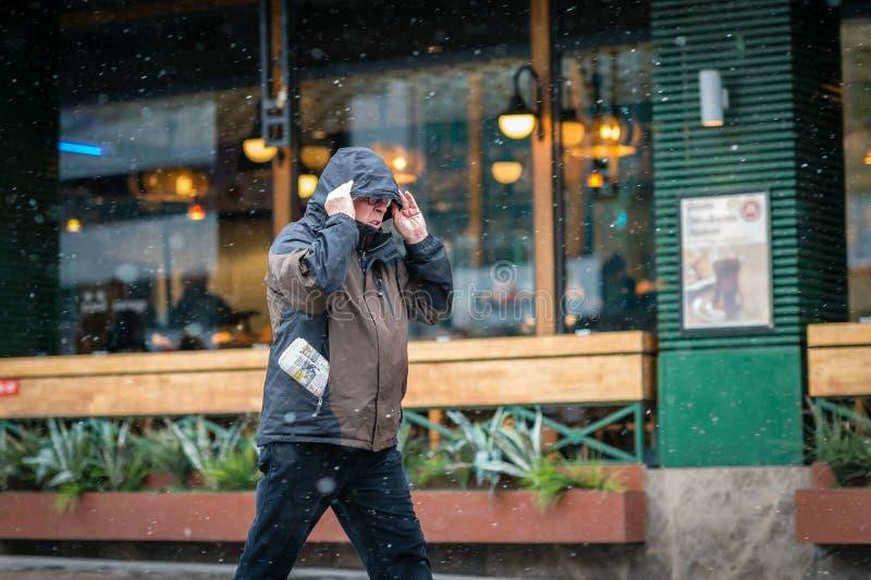 Homme dans la ville marchant tout en neigeant images stock
