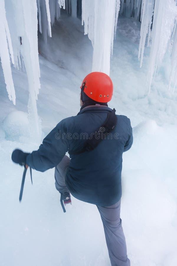 Homme dans la vitesse s'élevante à la cascade congelée de Pericnik dans Vrata valle photographie stock libre de droits