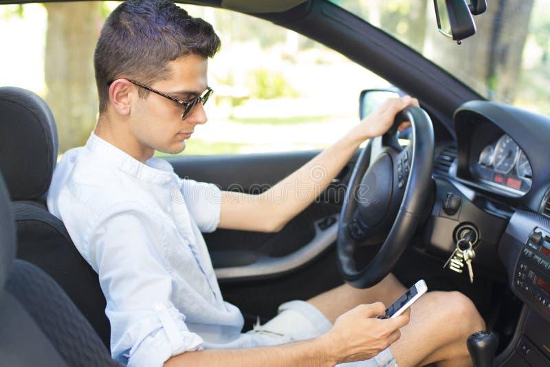 Homme dans la voiture regardant le téléphone portable image stock