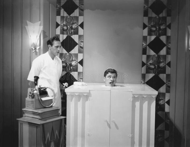 Homme dans le bain d'eau bouillante avec l'assistant et dictaphone (toutes les personnes représentées ne sont pas plus long vivan photographie stock