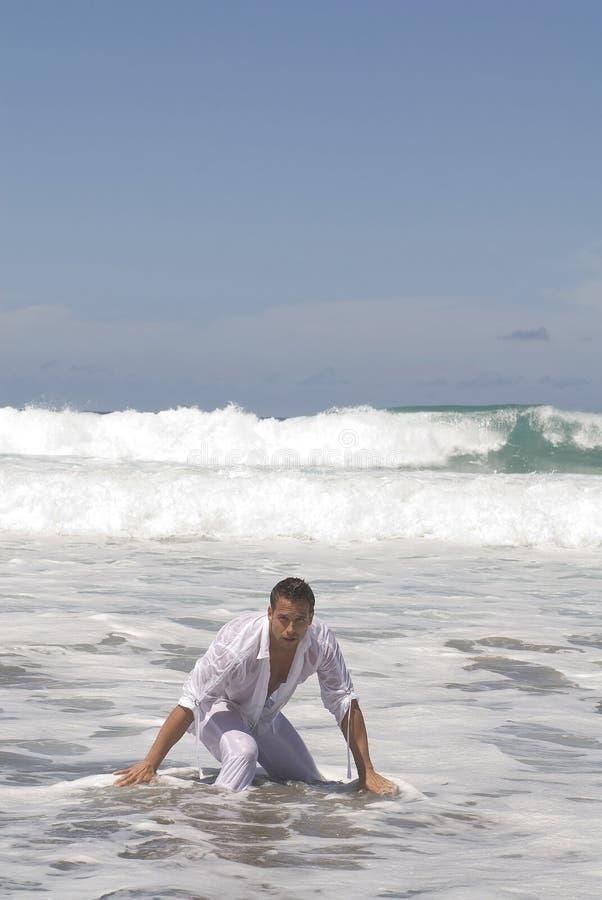 Homme dans le bord de la mer après un accident de bateau image stock